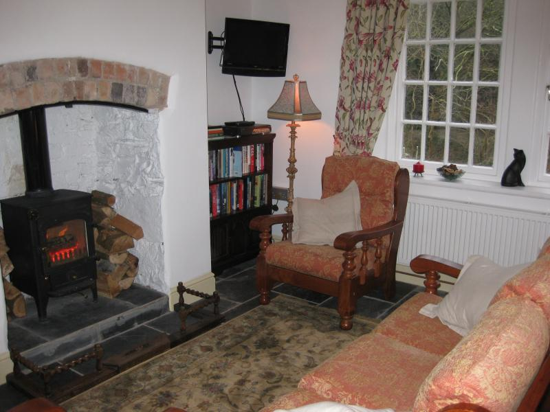 Comfortable living room with wood burning stove set into inglenook fireplace