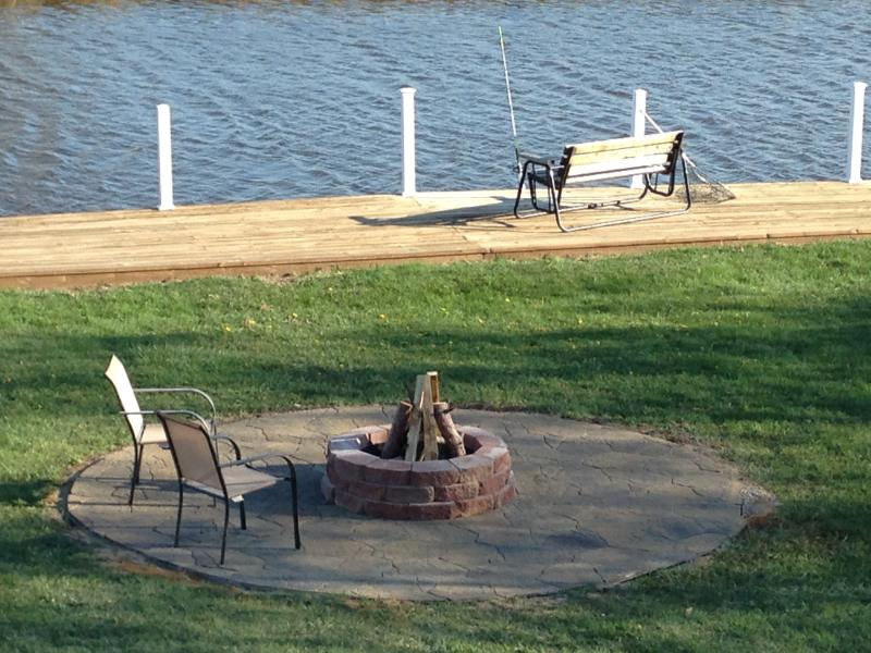 Fire pit area for evening bonfires.  Glider swing and fishing pole holder on dock.