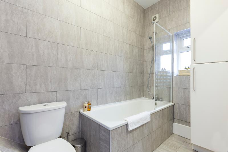 Bathroom with tiles, large mirror, bath and shower, radiator
