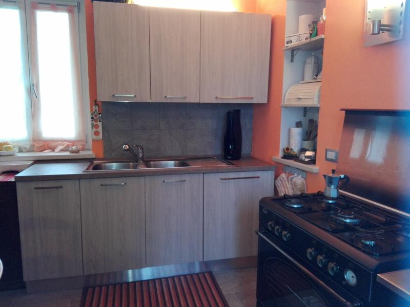 The kitchen contains a large oven, a washing machine and some useful appliances.