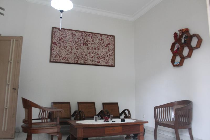 Front living room with batik wall decoration and antique wooden furniture