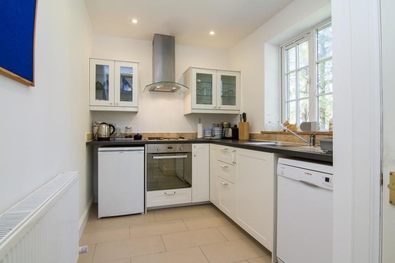 Kitchen with washing machine, dishwasher, electric hob, extractor hood.