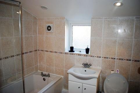 Bathroom: Bath with shower head, washing basin and toilet