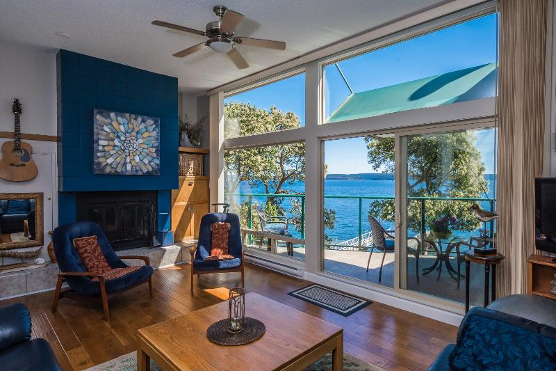 Large living room looking onto deck and ocean.