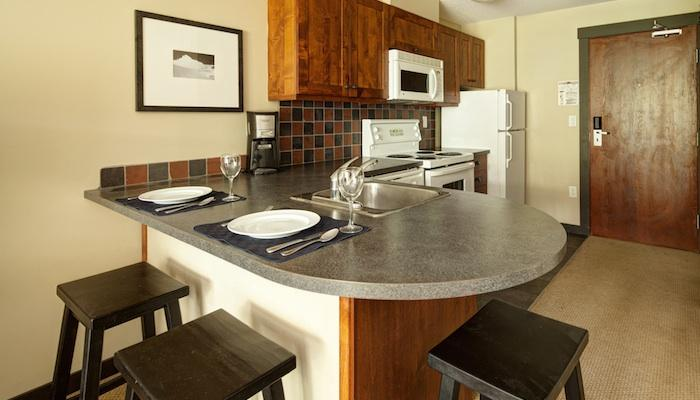 The kitchen area comes fully-equipped and features a breakfast bar