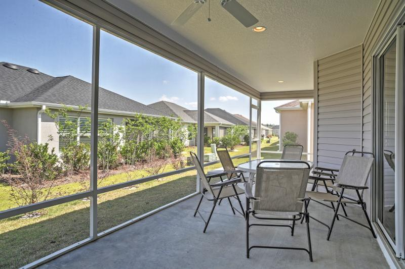 Lounge on the screened patio at this Florida vacation rental home.