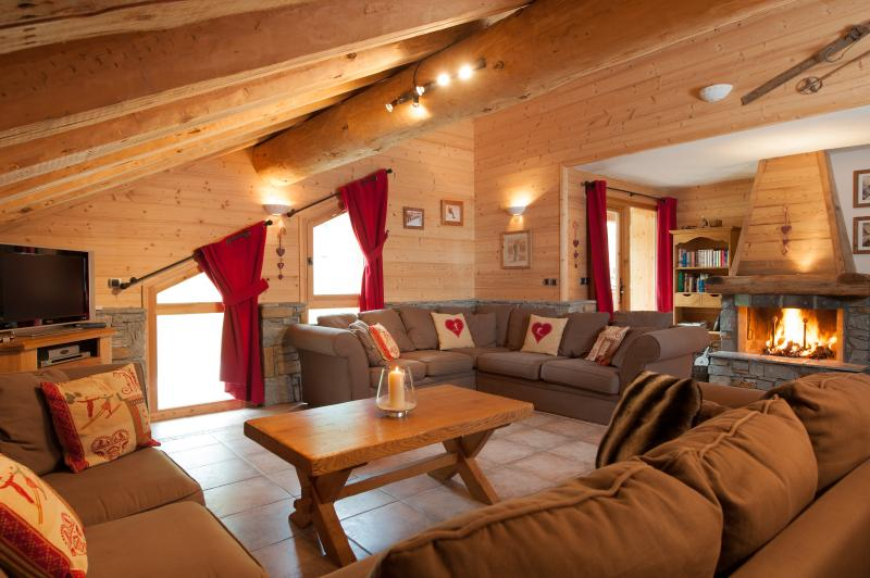 The spacious living room in Chalet La Vanoise with beautiful log fire