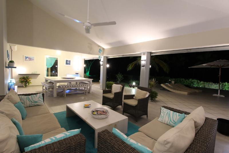 Outdoor salon and dining table at night