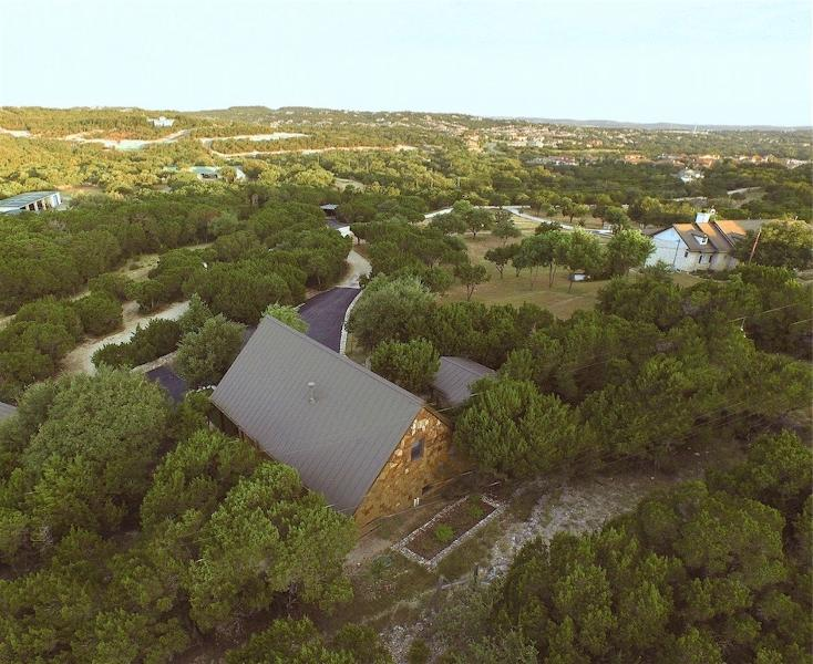 An aerial view of the Storybook Cottage & hill country beyond. The owners' main house is top right.