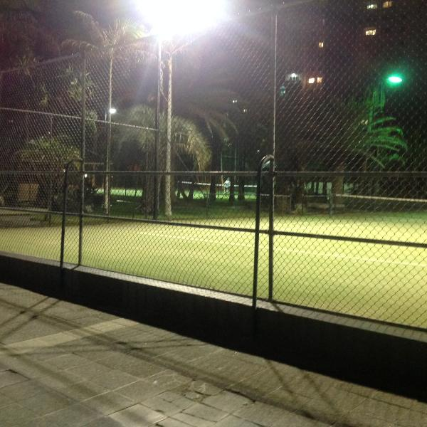 Tennis courts are floodlit at night for a hit in the evening.