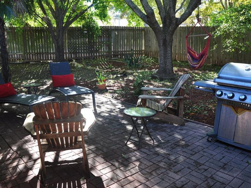 Shaded backyard with grill and seating area