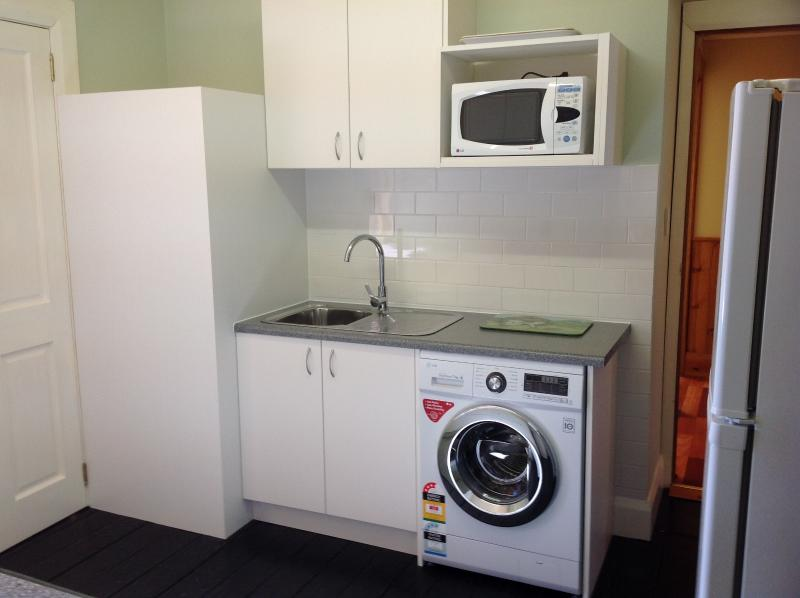 Kitchenette with washing machine and outside line.