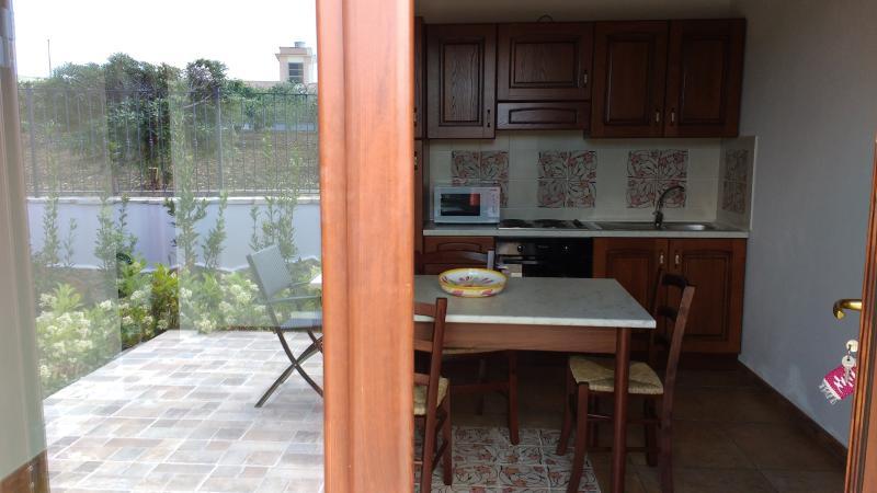 Cucina abitabile con tavolo, sedie, piastre elettriche, pentolame, microonde, forno, frigorifero, tv