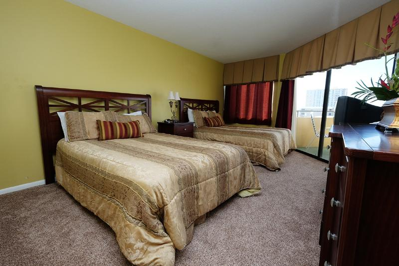 Guest bedroom with two full beds and balcony access