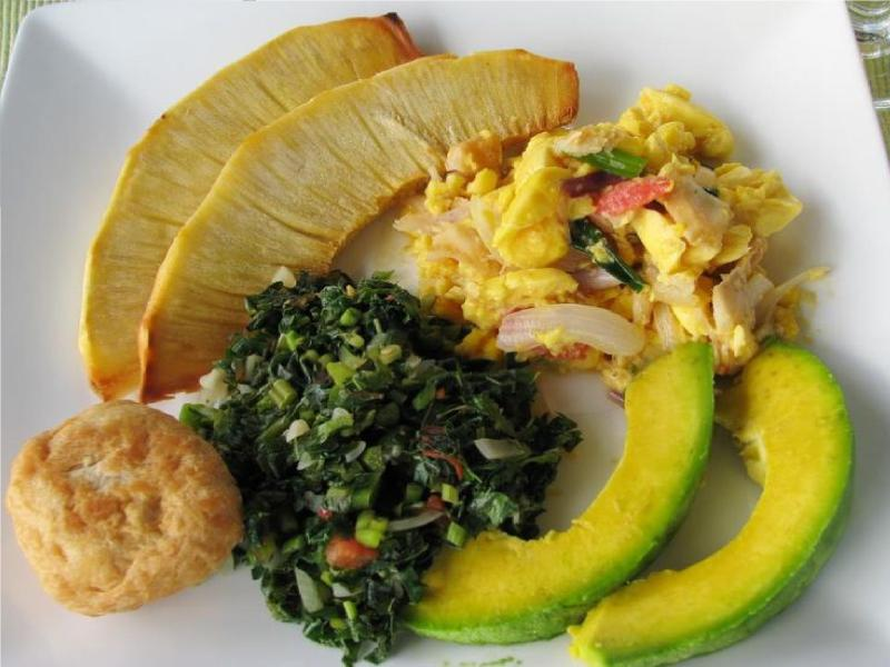 Meal of breadfruit, ackee and salted fish(national dish), callaloo, fried dumpling and avocado pear.