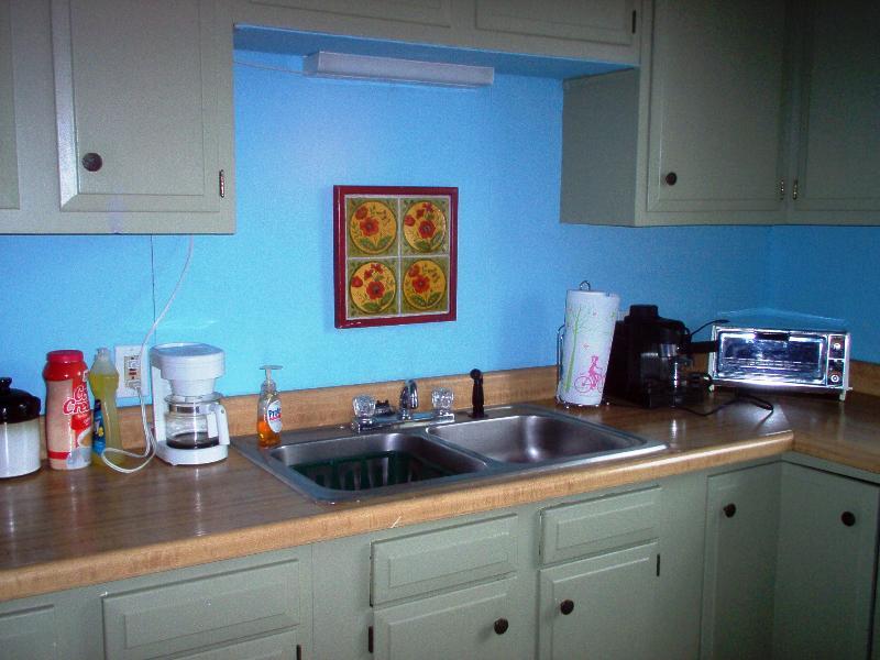 Kitchen with coffee pot, espresso machine, toaster, coffee, tea, creamer, and sugar.