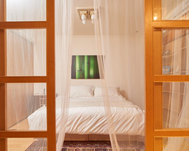 Dormitorio principal con entrada propia, puertas de vidrio cerradas con cortinas.