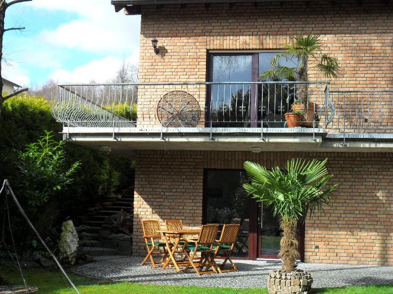 Ferienhaus mit Blick auf die Terrasse mit Tisch und vier Stühlen