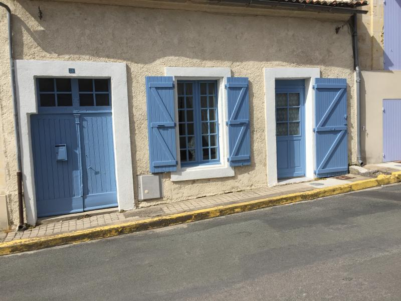 Traditional front painted blue, with working shutters, on a quiet road leading to the Marina