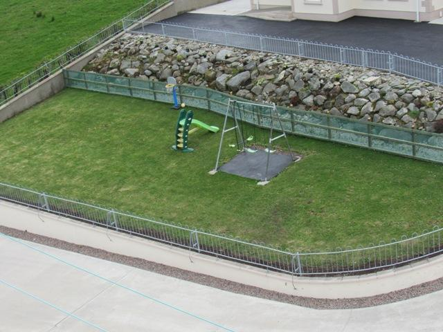 Kids play area with swing, slide and basketball ring.