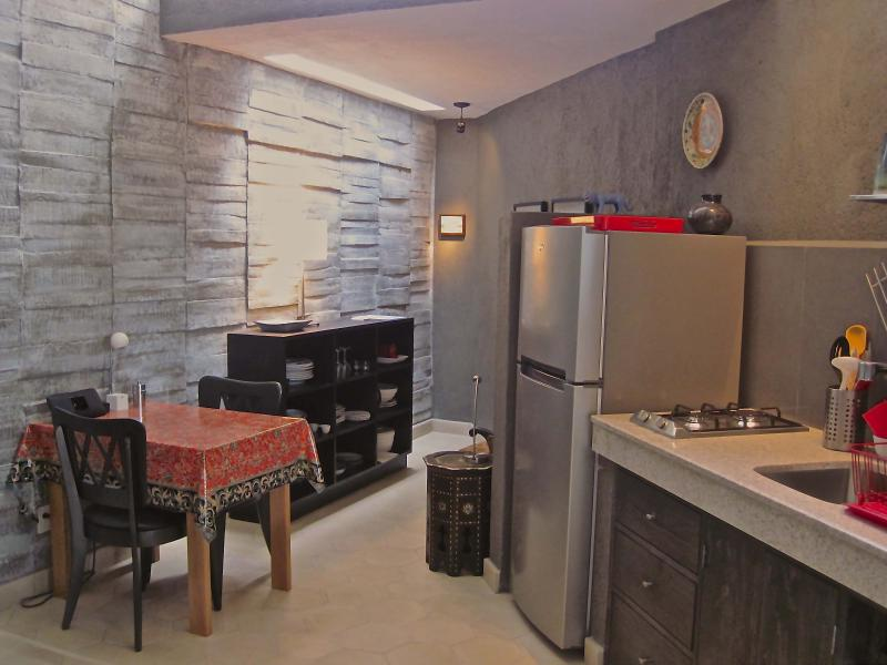 Kitchen with reading nook located behind refrigerator on the right and dining area.