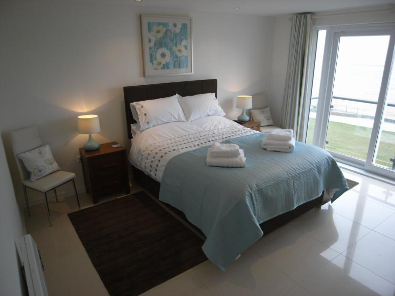 The master bedroom has a balcony overlooking the beach and an en suite shower room