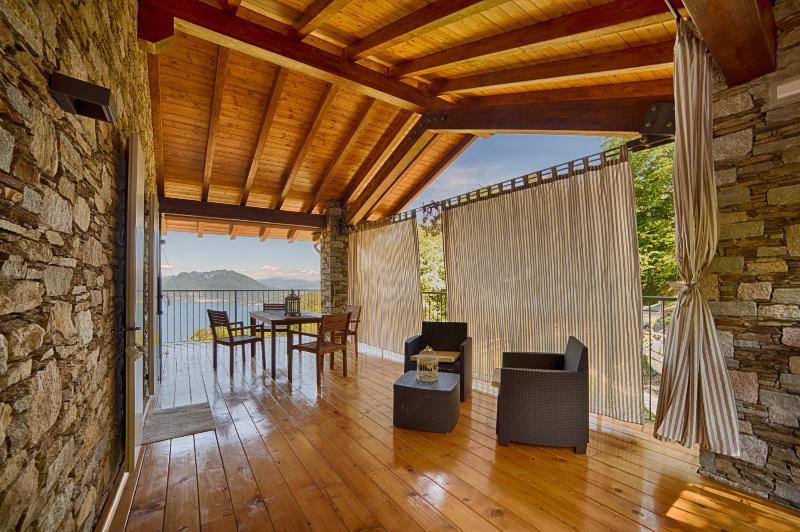 terrazzo con zona pranzo e zona relax e dettaglio tende per maggior privacy