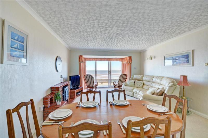 Spacious lounge with dining area and patio doors.
