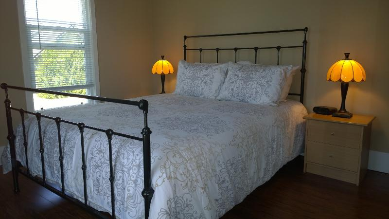 Large bedroom with comfy queen bed, two nightstands, alarm clock w/ USB port, armoire, luggage rack.