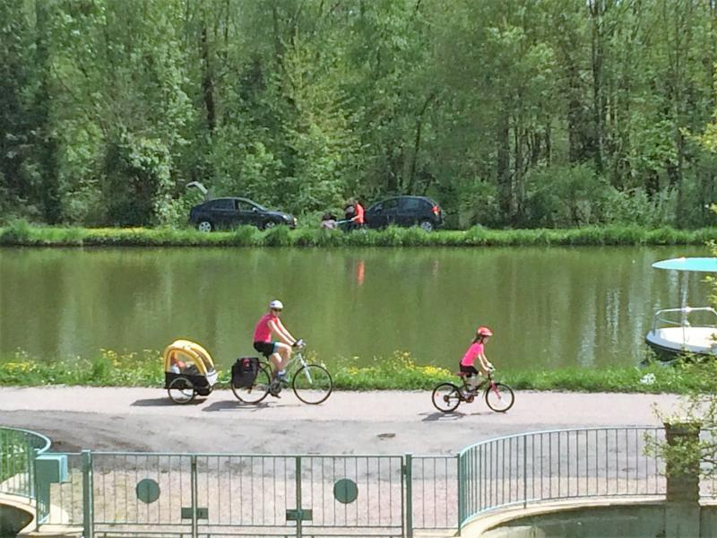 Ciclo de la diversión para toda la familia o ver a los ciclistas, excursionistas y barcos del canal de la villa