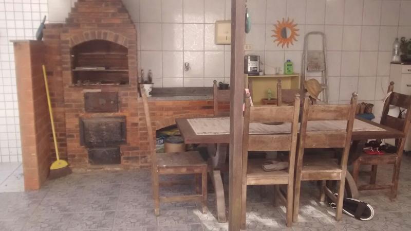 Quintal com mesa para 6 pessoas, churrasqueira e lavanderia.