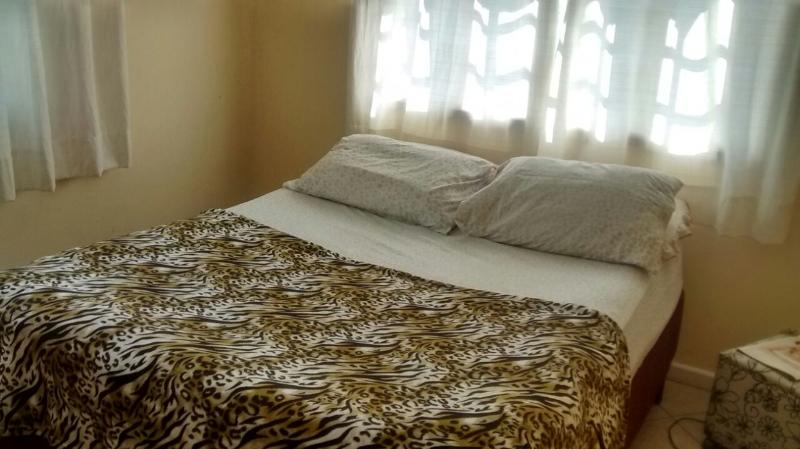 Quarto com cama de casal, ar condicionado e televisão.
