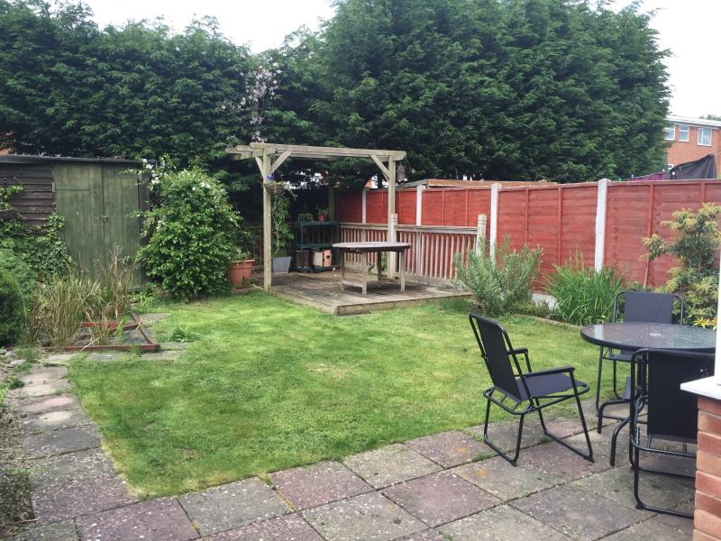 The garden with a lawn, decking, patio and covered pond.