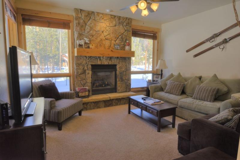 Living Room - The living room features a natural stone fireplace and a flat screen TV.