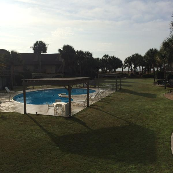 Common pool in grassy courtyard. Beach just through the palm trees. Easy walk with access all tides