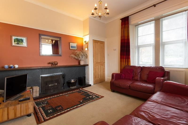 The comfortable sitting room has an open fire for cozy evenings in.