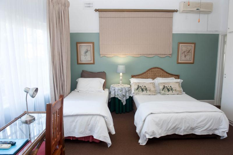 Green bedroom. This bedroom has a queen and single bed. The en-suite bathroom has a bath and shower
