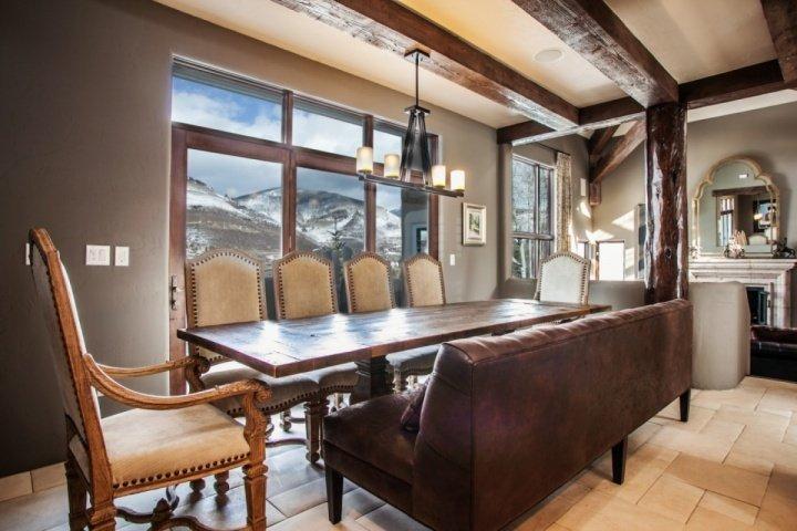Situé à côté de la cuisine, une grande table à manger pour 10 avec des sièges banc surdimensionné et vue sur la montagne magnifique.