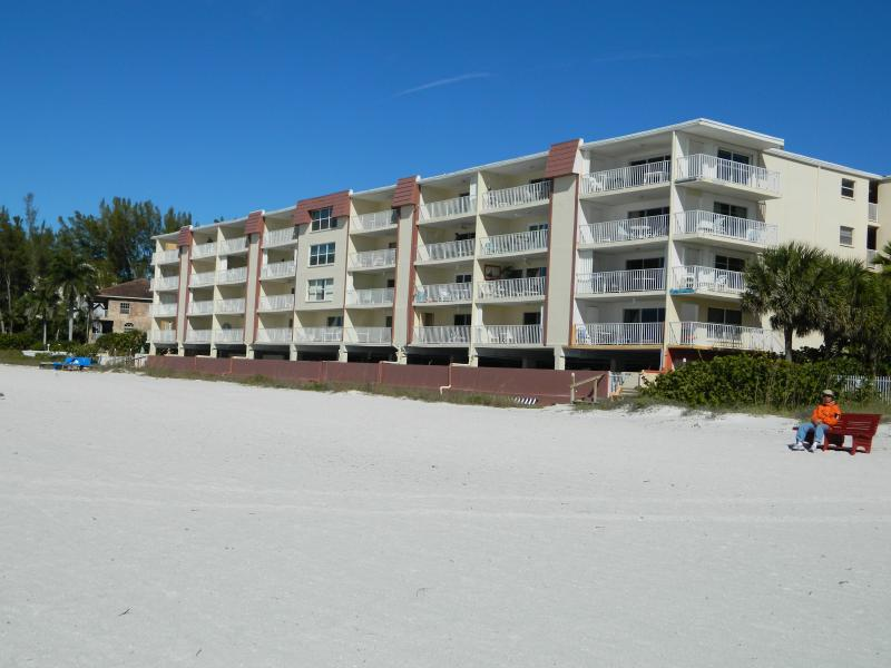 View of building from beach. The condo is located on the first floor and third from the right side.