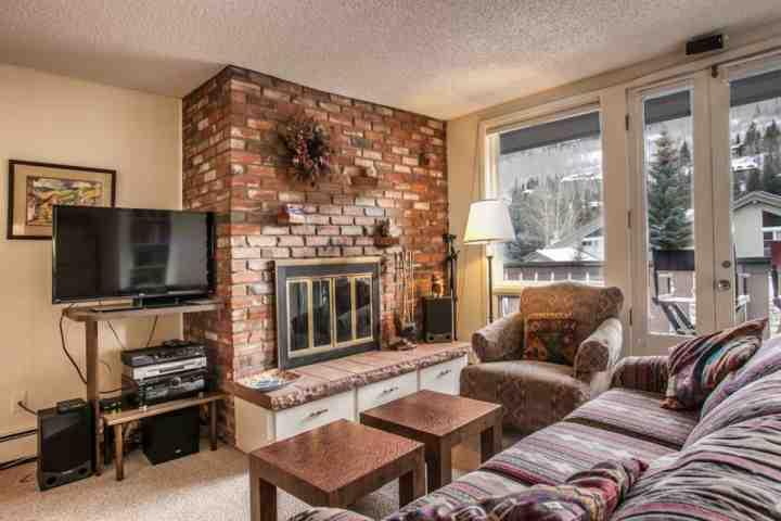Living room with wood burning fireplace, 38' flat screen TV/DVD and mountain views.