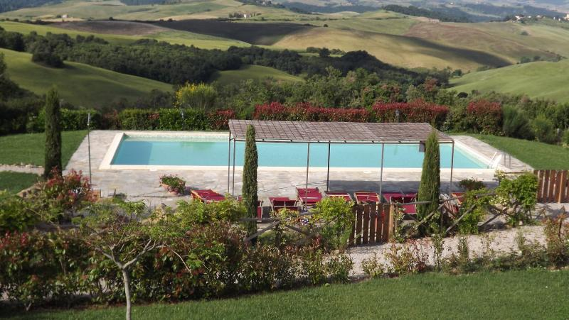 The pool surrounded by gardens and enjoying a panoramic view of the tuscan landscape
