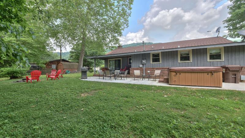 Back yard fun with covered back porch with 'dueling' swings, hot tub, gas grill & patio table.