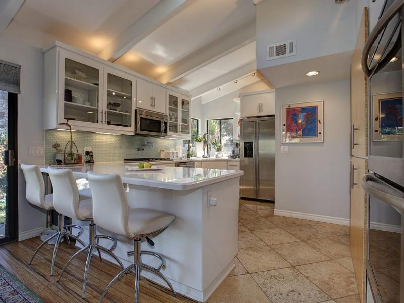 Kitchen with serving bar and barstools.