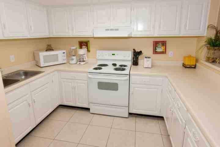 Betegelde keuken met een broodrooster, koffiezetapparaat, blender en aanrecht magnetron