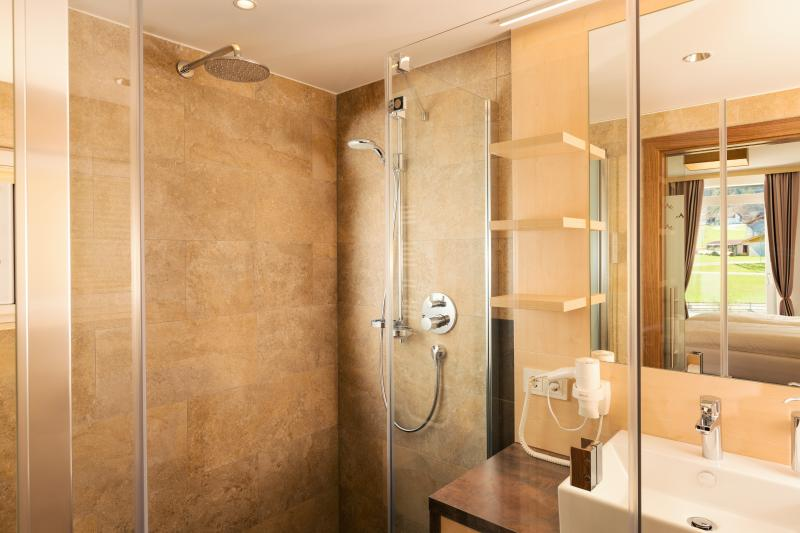 Wet room with power shower, wall and hand shower