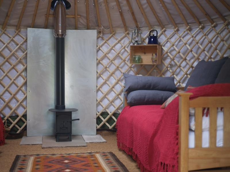 Wood-stove keeps the yurt warm and cosy, with two day beds either side.