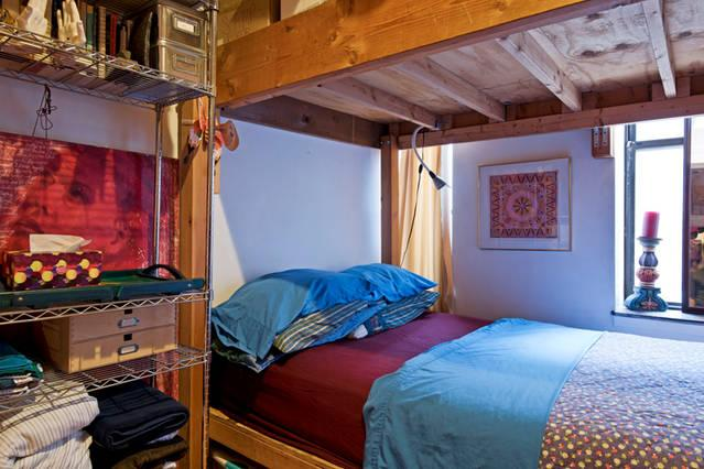 Comfortable bedroom -- brick walls and hardwood floors
