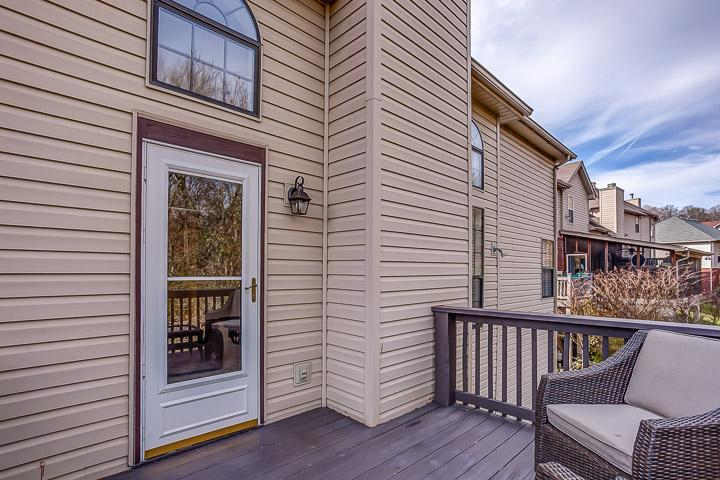 Back deck features wicker patio furniture and a gas grill.