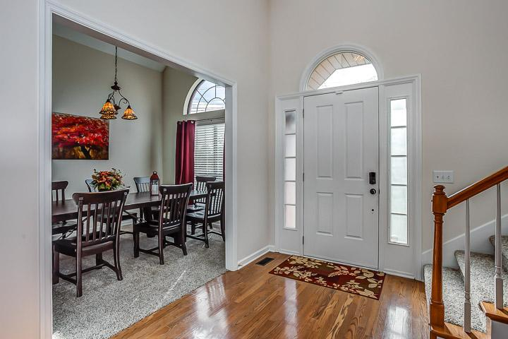 Open foyer with soaring ceilings and hardwood floor.