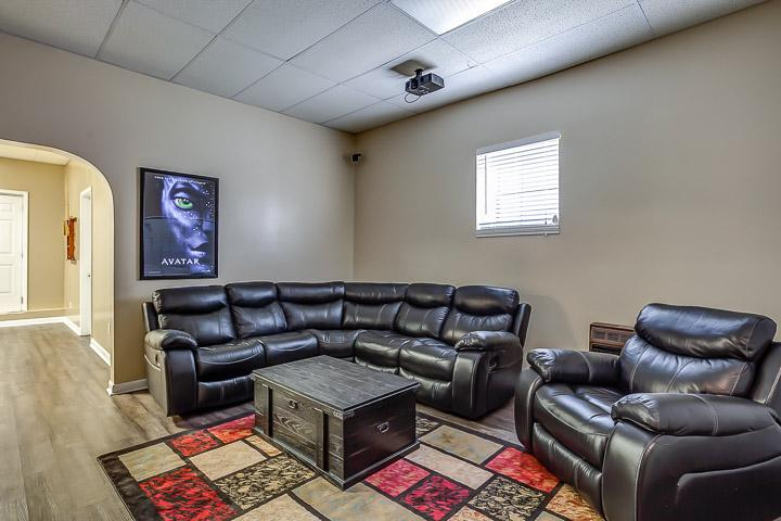 Theater room with 120' projector screen tv and leather sectional.